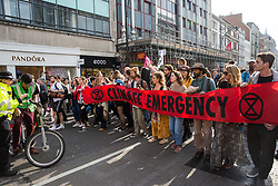 London, UK. 18th April 2019. Climate change activists from Extinction Rebellion march with the XR Samba Band from Marble Arch to Oxford Circus to foil a large police operation to attempt to clear Oxford Circus on the fourth day of the International Rebellion to call on the British government to take urgent action to combat climate change.