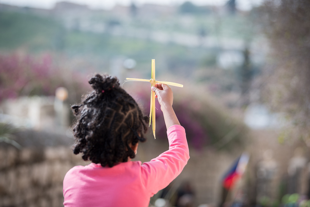 14 April 2019, Jerusalem: A young girl reaches toward Jerusalem, holding a palm leaf cross. On Palm Sunday, thousands gathered and marched from the Mount of Olives down to the Old City of Jerusalem, following in the footsteps of Jesus, as he journeyed to Jerusalem.