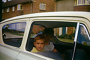 A young boy sits in the family Anglia car with his older sister on an Essex estate in the early nineteen sixties. Peering out of the open window the boy and girl are on their way out for a daytrip in their new car, a Ford Anglia.  This is the new age of car ownership when newfound wealth meant families could afford to buy a vehicle and travel elsewhere after the war years of 1950s austerity. The Ford Anglia is a British car designed and manufactured by Ford in the United Kingdom. The Ford Anglia name was applied to four models of car between 1939 and 1967. 1,594,486 Anglias were produced. The picture was recorded on Kodachrome (Kodak) film in about 1961.