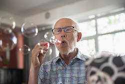 Senior man blowing bubbles at rest home, Bavaria, Germany, Europe