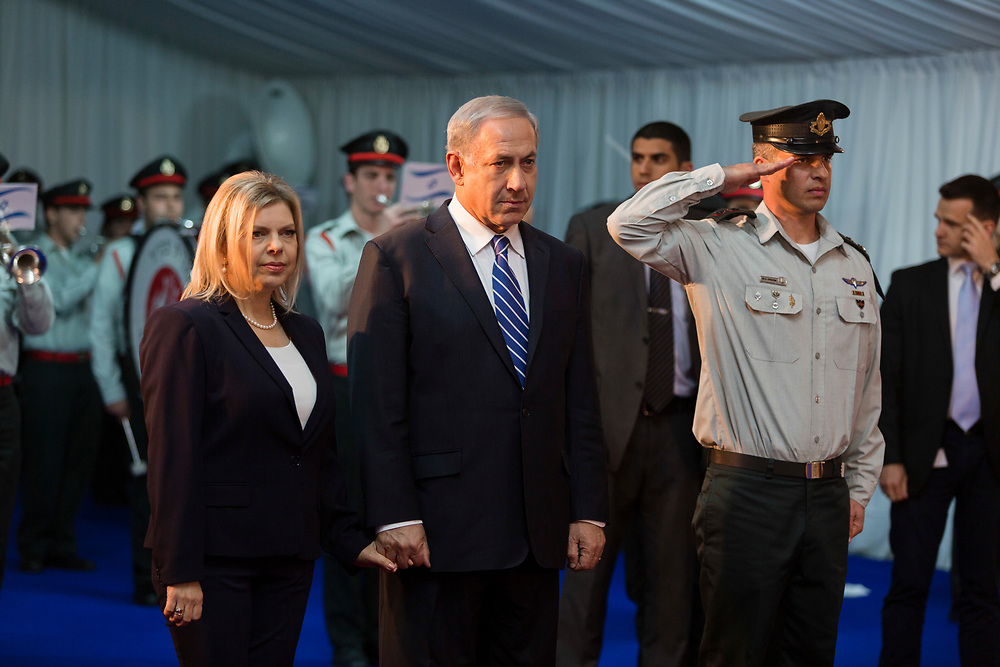 Israeli Prime Minister Benjamin Netanyahu (C) and his wife Sara (L) attend an official welcoming ceremony for Canada's Prime Minister (not pictured) at the Israeli Prime Minister office in Jerusalem, on January 19, 2014. Canada's PM, Harper, is on four-day visit to  Israel and the Palestinian Territories, the first by a serving Canadian Prime Minister since 2000.