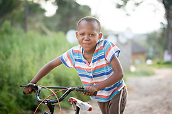 """2 March 2017, Morija, Maseru district, Lesotho: A boy walks by Scott Hospital with his bike. The hospital is run by the Lesotho Evangelical Church in Southern Africa and is a founding member of the Christian Health Association of Lesotho. It is located in the village of Morija, and operates and supervises clinics in the Maseru District of Lesotho. Scott started out as a dispensary in 1864, and today offers comprehensive healthcare Mondays-Fridays, as well as pharmaceutical services around the clock. Lesotho suffers from high numbers in Tuberculosis in disesase and mortality, and so the hospital screens all patients for TB. The hospital observes among many patients what they describe as """"low health-seeking behaviour"""", services are increasing and demand rising, but space and human resources are a challenge, as is funding. I key concern is one of infrastructure, where the original design of the hospital matches poorly with current needs, as departments and buildings are scattered, posing a challenge for security. Another challenge is to adapt donation structures, so as to be able to receive payments electronically. The hospital has one ambulance, which they describe as not enough, but what they have. Another challenge is that lack of funds affects maintenance of buildings and infrastructure, as the immediate care of patients take priority. PLEASE NOTE: This photo is not to be used in social media."""