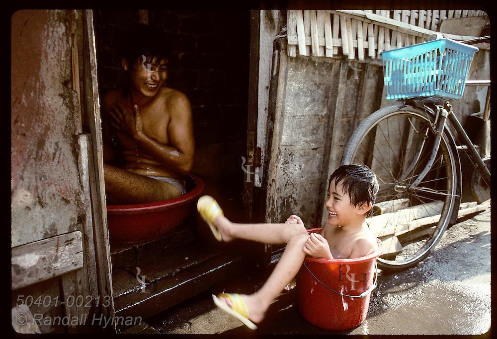 Boy in bucket and man in wash basin bathe at their bamboo shack in poor neighborhood of Shanghai China