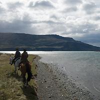 Chilean gauchos ride by Lago de Toro in Torres del Paine National Park, Patagonia, Chile.