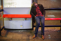 "© licensed to London News Pictures. London, UK 14/12/2013. A ""Mad Friday"" reveller falls asleep on a bus stop in central, London whilst enjoying the last Friday night out before Christmas, which is also the busiest night of the year for emergency services. Photo credit: Tolga Akmen/LNP"