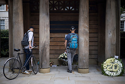 © Licensed to London News Pictures. 11/09/2021. London, UK. Members of the public look at flowers flowers left at a memorial in Grosvenor Square in London on the 20th anniversary of the 9/11 terrorist attack. The attacks, which killed a total of 2,977 people, saw passenger jets seized by suicide attackers, flown into the Twin Towers of the World Trade Center in New York and the The Pentagon building. Photo credit: Ben Cawthra/LNP