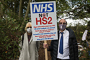 Two anti-HS2 activists stand with a NHS Not HS2 placard during evictions by National Eviction Team bailiffs working on behalf of HS2 Ltd from a wildlife protection camp in the ancient woodland which inspired Roald Dahl's Fantastic Mr Fox at Jones' Hill Wood on 1 October 2020 in Aylesbury Vale, United Kingdom. Around 40 environmental activists and local residents, some of whom living in tree houses 60 feet above the ground, were present during the evictions at Jones' Hill Wood which had served as one of several protest camps set up along the route of the £106bn HS2 high-speed rail link in order to resist the controversial infrastructure project.