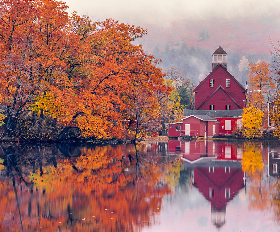 Old red mill on misty fall morning, reflections in Squam River, Ashland, NH