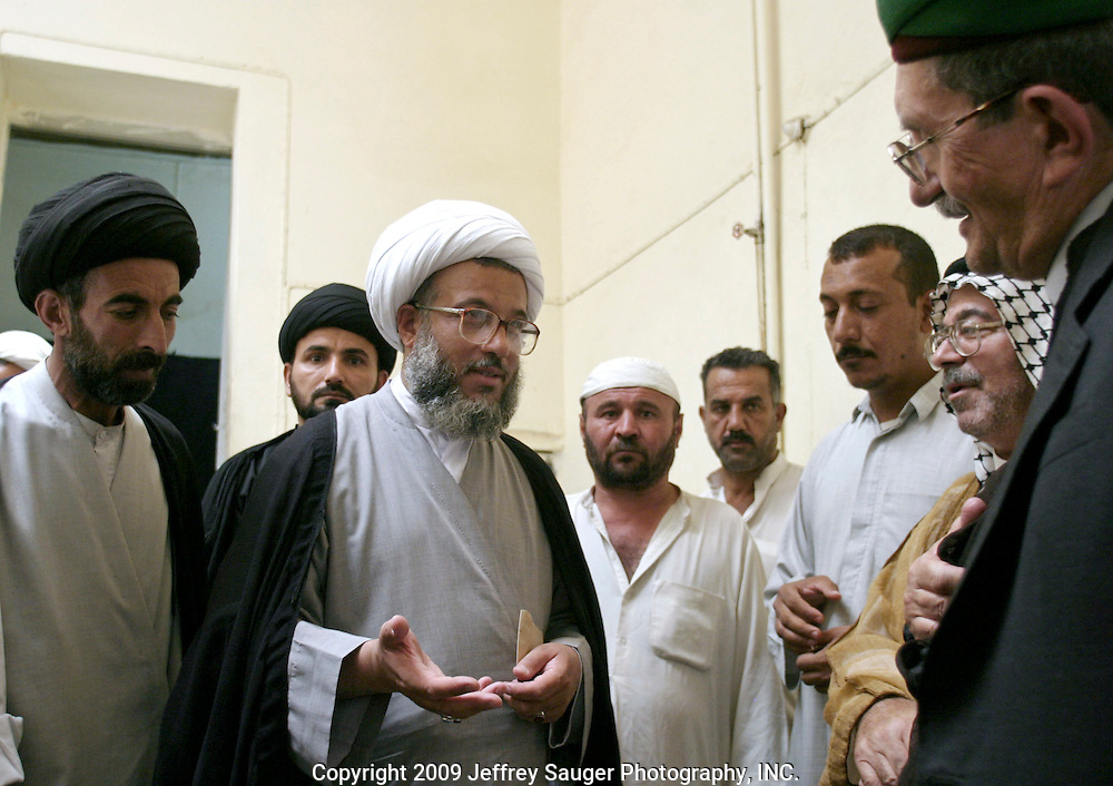 """Sheik Abdul Mahdei Abdul Ameereir Al Salemey, far right facing camera with gray beard, meets with religious men and students at his house in Karbala, Iraq, Tuesday, July 22, 2003. """"We the Shiite,"""" he said."""" We need to have our own rights. We not asking to be the government. We are asking to have a law to give the rights to all Iraqi people; Shiite, Kurdish, Sunni, and Christian."""" He is the first assistant for Ayottallah Ali Sistani. Sistani is the highest Shiite leader for all of Iraq."""
