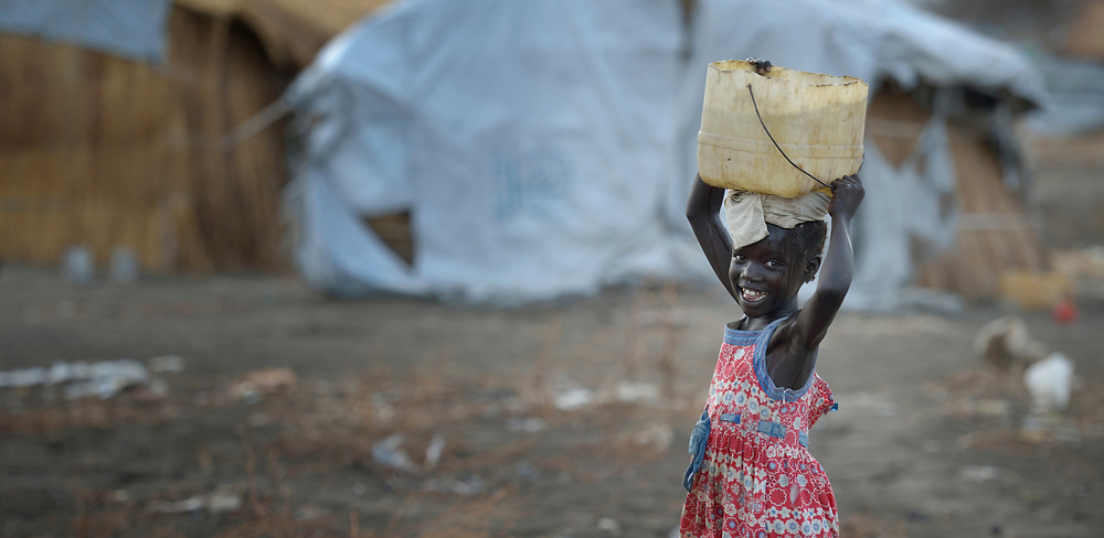 A girl carries home water from a well constructed by Caritas in a displaced persons camp in Agok, South Sudan. Tens of thousands of residents of Abyei, a contested region along the border between Sudan and South Sudan, remain displaced in Agok. Under a 2005 peace agreement, Abyei was supposed to have a referendum to decide which country it would join, but the two countries have yet to agree on who can vote. In 2011, militias aligned with Khartoum drove out most of Abyei's Dinka Ngok residents, pushing them across a river into the town of Agok. More than 40,000 Dinka Ngok have since returned to Abyei with support from Caritas South Sudan, which has drilled wells, built houses, opened clinics and provided seeds and tools for the returnees. Yet continuing insecurity means a greater number remain in Agok, where they remain dependant on Caritas and other organizations for food and other support.