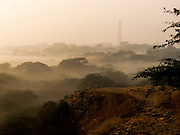 29th November 2015, New Delhi, India. Early morning view in Sanjay Van from the top of the ancient Qila Lal Kot wall towards Qutub Minar in New Delhi, India on the 29th November 2015<br /> <br /> The Qila Lal Kot is a wall that was built around the first city of Delhi when it was established in the 8th century by Tomar Rajputs. Later, the Chauhans added to the fortification in the 12th century and its the ruins of this which can still be seen in Sanjay Van forest in Delhi <br /> <br /> PHOTOGRAPH BY AND COPYRIGHT OF SIMON DE TREY-WHITE<br /> <br /> + 91 98103 99809<br /> email: simon@simondetreywhite.com<br /> photographer in delhi