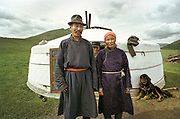 A Mongolian family, (husband, wife and brother in the back), with their shepherd dog stand in front of their yurts close to Karakoram. They wear their traditional  Mongolian robe called a del.