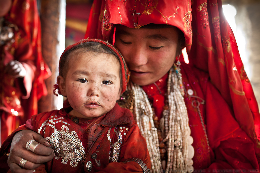 Ikhbal (15, Right) with her younger sister..The veil celebration: before moving to her new husband's camp, Ikhbal, a recently married Kyrgyz girl, will exchange the red veil of the unmarried girl for the white veil signifying that she is now a married woman...The Kyrgyz settlement of Ech Keli, above Chaqmaqtin lake, Er Ali Boi's camp...Trekking through the high altitude plateau of the Little Pamir mountains, where the Afghan Kyrgyz community live all year, on the borders of China, Tajikistan and Pakistan.