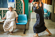 "11 JANUARY 2013 - BANGKOK, THAILAND: Boys do exercises after being caught misbehaving on their way to Mosque for noon prayers in the Ban Krua neighborhood in Bangkok. The Ban Krua neighborhood of Bangkok is the oldest Muslim community in Bangkok. Ban Krua was originally settled by Cham Muslims from Cambodia and Vietnam who fought on the side of the Thai King Rama I. They were given a royal grant of land east of what was then the Thai capitol at the end of the 18th century in return for their military service. The Cham Muslims were originally weavers and what is known as ""Thai Silk"" was developed by the people in Ban Krua. Several families in the neighborhood still weave in their homes.                   PHOTO BY JACK KURTZ"