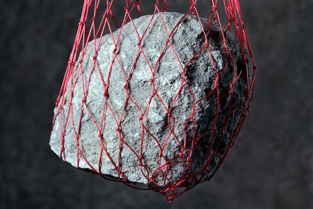 heavy stone hanging in a strong plastic netting