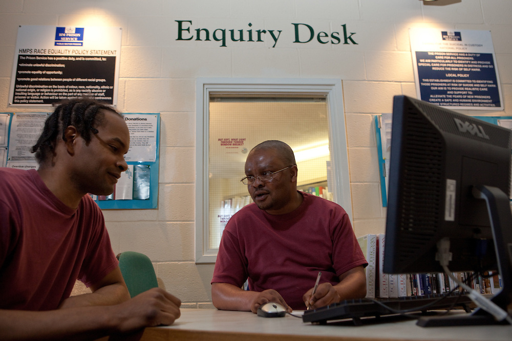A prisoner working on the enquiry desk of the prison library helps a fellow inmate. HMP The Mount, Bovingdon, Hertfordshire