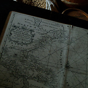 """A copy of an 18th Century chart showing the """"Western"""" (now known as the Atlantic) ocean and the coasts of North and South America lies open on top of a table with a few barrels of supplies in the background. If one were to undertake a transatlantic voyage in those days, it would require preparation, guts and lots of planning."""