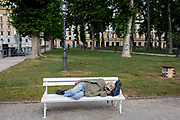 A man sleeps on a bench in Congress Square in the Slovenian capital, Ljubljana, on 25th June 2018, in Ljubljana, Slovenia.