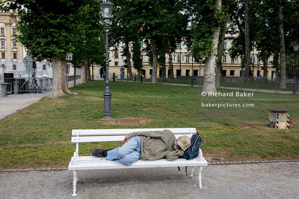 A man sleeps on a bench in Congress Square in the Slovenian capital, Ljubljana, on 25th June 2018, in Ljubljana, Slovenia.