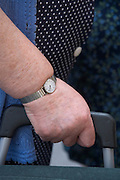 hand of an obese elderly person holding a shopping bag on wheels