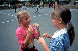 Deaf primary school girls using sign language in the playground