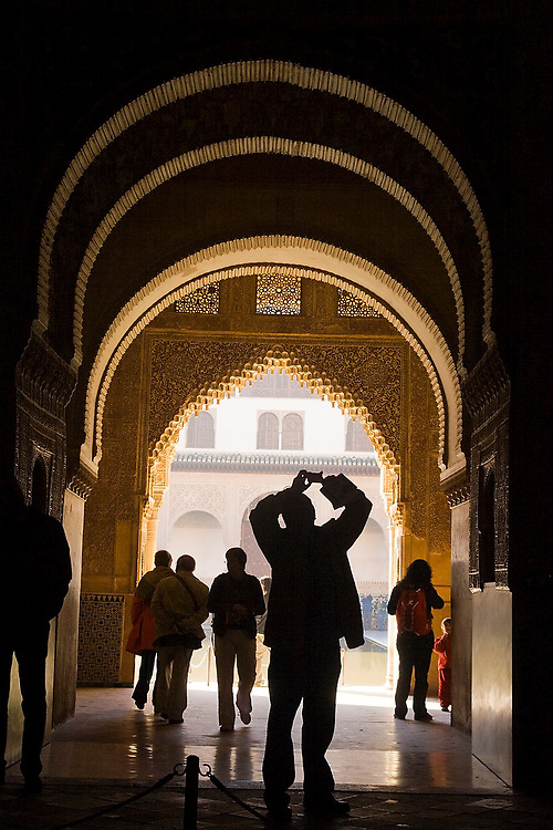 Visitors walk under and photograph a series of decorative stone carved arches in the entrance to the Casa Real complex, La Alhambra, Granada, Andalusia, Spain.