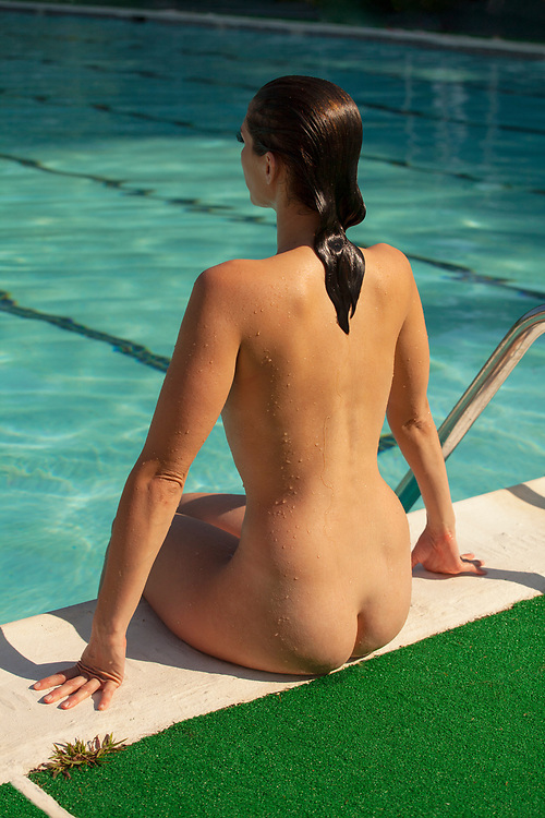 Nude woman sitting on the edge of a swimming pool with hands on pool edge.