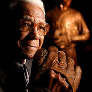 Buck O'Neil, a Kansas City legend for his career with the Kansas City Monarchs baseball team in the Negro Leagues, celebrates his 91st birthday Wednesday. O'Neil's birthday wish is to set a one-month attendance record at the Negro Leagues Baseball Museum, where this portrait was taken on Tuesday. The statue at background right is Satchel Paige. (David Eulitt/Kansas City Star)