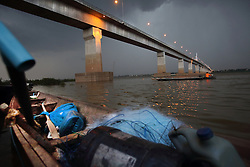 Small fishing boats on the Mekong River close to the Friendship Bridge between Savannakhet and Mukdahan Province of Thailand, just as a storm is rolling in.  The bridge is 1600 metres long.  Photographed from Lao PDR