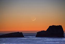 A crescent Moon sets off the rocky shore of San Simeon California.