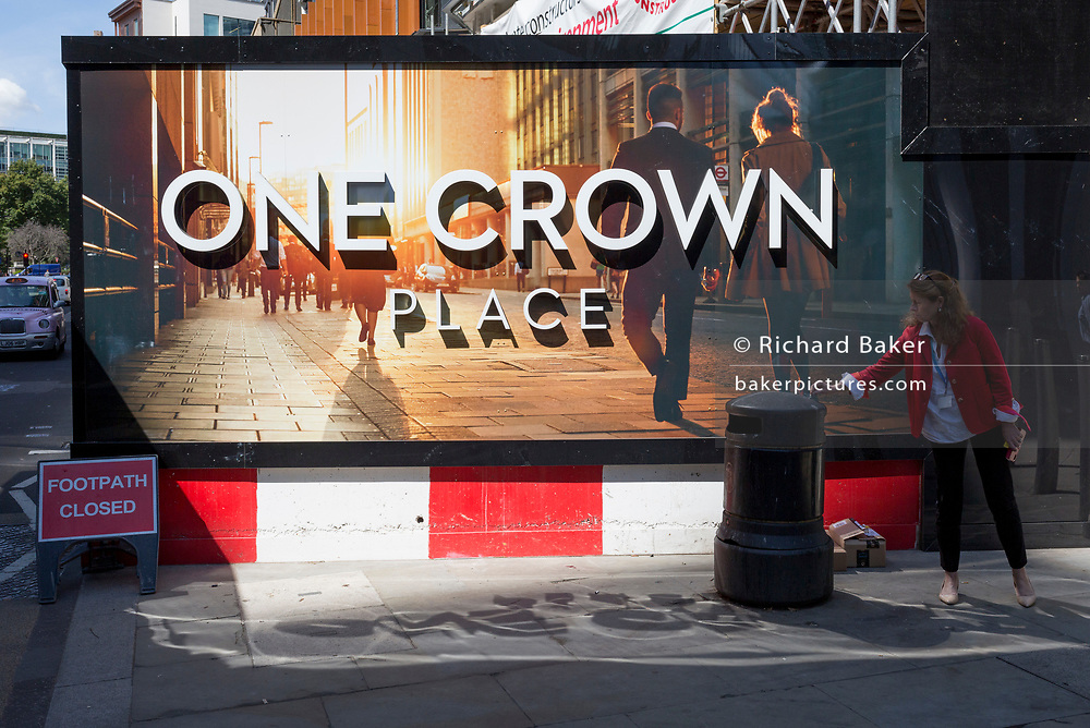 With a sign warning that the footpath (sidewalk) is closed, a smoker stubs her cigarette out beneath a construction hoarding at a new development called One Crown Place on Sun Street near Liverpool Street Station in the City of London, the capital's financial district - aka the Square Mile, on 8th August, in London, England.
