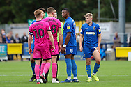 AFC Wimbledon defender Paul Kalambayi (30) talking to Rochadale attacker Aaron Wilbraham (18) with AFC Wimbledon midfielder Max Sanders (23) rubbing his thigh during the EFL Sky Bet League 1 match between AFC Wimbledon and Rochdale at the Cherry Red Records Stadium, Kingston, England on 5 October 2019.