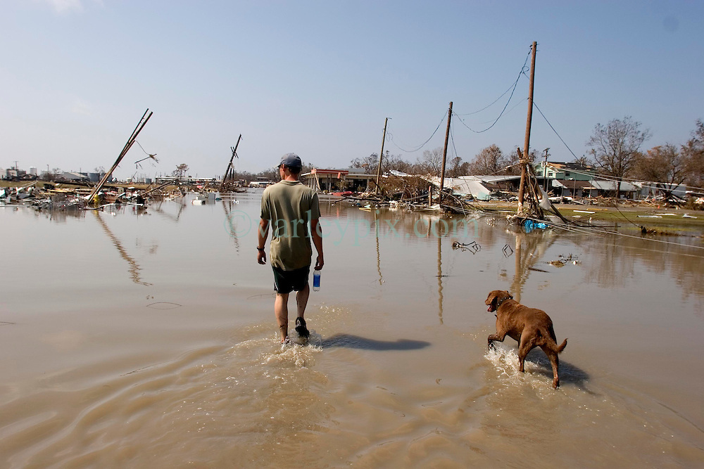 26th Sept, 2005. Hurricane Rita aftermath, Cameron, Louisiana. The destroyed remains of a downtown business in Cameron, Louisiana two days after the storm ravaged the small town. local man Aaron Stokes from nearby Carlyss surveys the damage with his dog Maggie.