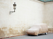A car parked and covered outside a mosque in the medina of Marrakech in Morocco