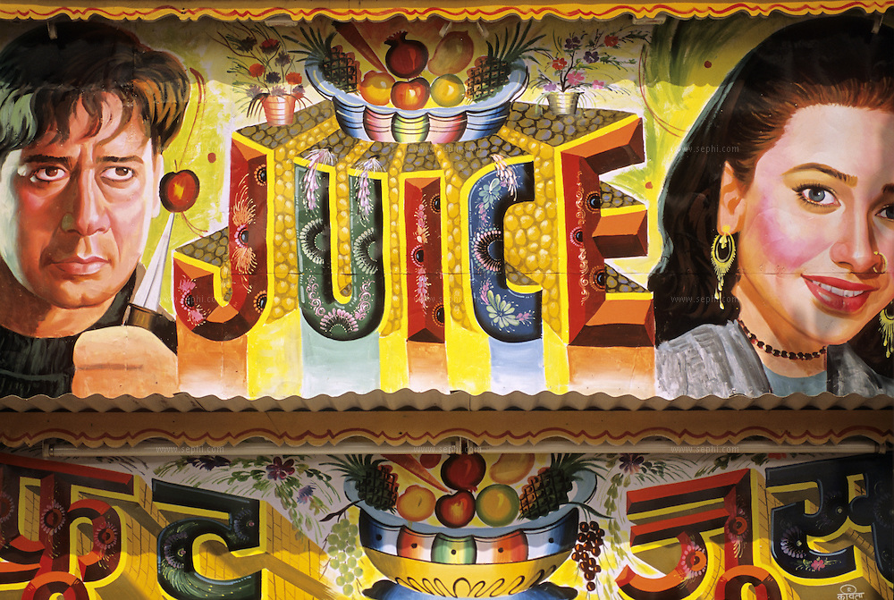 A poster depicting two Bollywood stars, Ajay Devgan (left) and Karishma Kapoor, outside a juice stall in New Delhi.