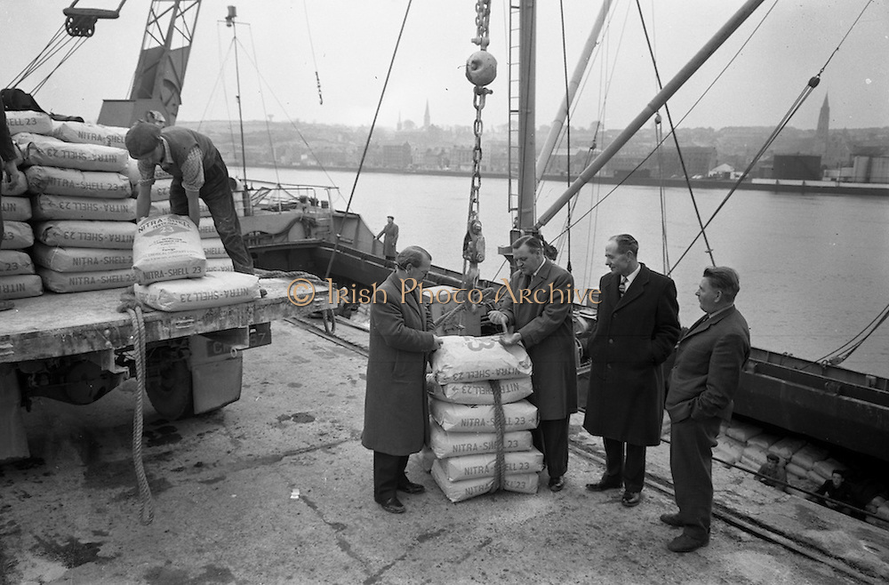 """11/02/1963<br /> 02/11/1963<br /> 11 February 1963<br /> Nitra-Shell 23 cargo discharged at New Ross, Co. Wexford. The """"M.V. Roelf Buisman"""" from Rotterdam on it's first visit to New Ross delivering 500 ton of Nitra -Shell 23 the first consignment of 23% Nitrogen imported into Ireland. Messrs. Albatross Windmill Fertiliser Co. Ltd. were the importers. Picture shows, looking at some of the Nitra-Shell 23 (l-r): Mr. J.J. Boyle, General Manager of Shell and Albatross (Agricultural) Ltd.; Mr. E.F. Storey, Managing Director, Albatross Windmill Fertiliser Co. Ltd.; Mr. M. Murphy, Manager J.J. Stafford (New Ross) and Captain  Smith of the """"Roelf Buisman""""."""