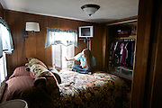 "Karly, daughter of Lance Frederick, owner of the custom harvesting company, in the family trailer. They live and travel in this trailer for about 7 months of the year...Life of custom harvesters: custom harvesting or custom combining is the business of harvesting of crops for others. Custom harvesters usually own their own combines and work for the same farms every harvest season. Custom harvesting relieves farmers from having to invest capital in expensive equipment while at the same time maximizing the machinery's use. .Harvesters travel North to South through the US, living in trailers, following the season, usually hiring overseas seasonal workers in need of improving their harvesting experience on very large combines (harvesting machines)...A 4-weeks road trip across the USA, from New York to San Francisco, on the steps of Jack Kerouac's famous book ""On the Road"".  Focusing on nomadic America: people that live on the move across the US, out of ideology or for work reasons."