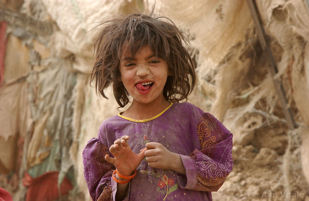 SPIN BOLDAK,AFGHANISTAN - SEPT. 4: An Afghan child from the Kuchi nomadic tribe laughs despite the horrible living conditions in an encamptment near Spin Boldak, the border town between Pakistan and southern Afghanistan September 4, 2002.  The UNHCR is trying to relocate tens of thousands of internally displaced people at the same time as an estimated 1.6 million Afghan refugees return to Afghanistan. Ethnic Pashtuns and Kuchi nomads from northern Afghanistan are seeking safety in camps in the south. Numbering up to 120,000,  theys are fleeing the Tajik- and Uzbek-dominated cities of the north out of fear and prefer to live in the dismal camps like Zhare Dasht which is set in the middle of a desert surrounded by mines about 30 kilometers west of Kandahar. (Photo by Ami Vitale/Getty Images)