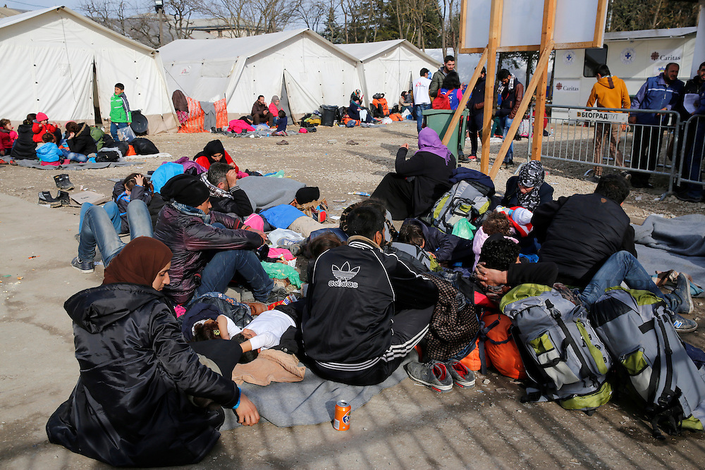 Migrants and refugees rest on the ground as they wait to continue their journey towards western Europe from the Macedonia-Serbia border at a transit camp in the village of Presevo, Serbia, February 2, 2016.<br /> Photo: Darrin Zammit Lupi