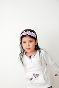 Portrait of a Young girl of 5 dressed in white with a mauve hairband