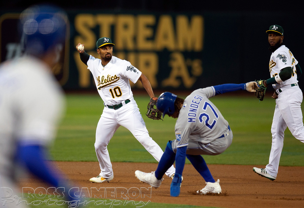 Sep 17, 2019; Oakland, CA, USA; Oakland Athletics shortstop Marcus Semien (10) throws over Kansas City Royals Adalberto Mondesi (27) during the first inning of a baseball game at Oakland Coliseum. Kansas City Royals designated hitter Jorge Soler (12) was out at first base. Mandatory Credit: D. Ross Cameron-USA TODAY Sports