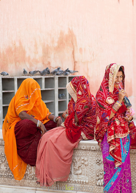 Women in colourful saris sit on a wall in Bikaner, Rajasthan, India