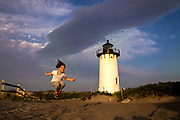 A joyful young girl jumps rope at Race Point Lighthouse in Provincetown, MA.