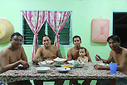 August 2012: Kelabit native family with guests. Now eating at a table, something unheard of decades ago. Sinang's family in their newly built home. However their community is threatened by a Mega hydro-electric dam project which will totally flood their valley, leaving them homless. Long Napir, Limbang district, Sarawak, Borneo<br /> <br /> The Limbang valley including Long Napir, a cluster of four settlements of Penan and Kelabit people, is threatened by a new hydro-electric project which will flood the entire area, displacing thousands of native people. The Murum Hydro-electric project already underway affecting the Rejang region, will displace over 24,000 Dayak native residents, destroying their longhouses and forest habitat. The dam site is located on the Murum River, in the uppermost part of the Rajang River basin, 200km from Bintulu. Sarawak's primary rainforests have been systematically logged over decades, threatening the sustainable lifestyle of its indigenous peoples who relied on nomadic hunter-gathering and rotational slash & burn cultivation of small areas of forest to survive. Now only a few areas of pristine rainforest remain; for the Dayaks and Penan this spells disaster, a rapidly disappearing way of life, forced re-settlement, many becoming wage-slaves. Large and medium size tree trunks have been sawn down and dragged out by bulldozers, leaving destruction in their midst, and for the most part a primary rainforest ecosystem beyond repair. Nowadays palm oil plantations and hydro-electric dam projects cover hundreds of thousands of hectares of what was the world's oldest rainforest ecosystem which had some of the highest rates of flora and fauna endemism, species found there and nowhere else on Earth