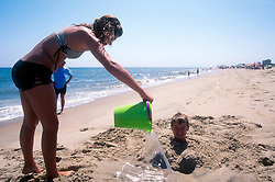 An unidentified girl dumps a bucket of sea water on her younger brother, buried in the sand at Cape Henlopen State Park in Rehoboth Beach, Del., Monday, Aug. 19, 2019 (Photo by D. Ross Cameron)