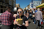 Young woman on Portobello Road enjoying a pineapple drink in Notting Hill, West London, England, United Kingdom. People enjoying a sunny day out hanging out at the famous Sunday market, when the antique stalls line the street.  Portobello Market is the worlds largest antiques market with over 1,000 dealers selling every kind of antique and collectible. Visitors flock from all over the world to walk along one of Londons best loved streets.