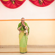 An older woman wearing a Sari dress poses for a portrait during a wedding reception.