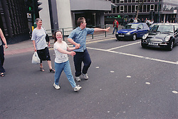 Teenage boy and girl with Downs Syndrome holding hands while crossing road at pedestrian crossing,