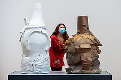 """© Licensed to London News Pictures. 27/09/2021. LONDON, UK. A staff member views (L) """"Voulkos #2"""", 2021, by Theaster Gates, inspired by (R) """"Pinatubo"""", 1994, by Peter Voulkos . Preview of """"A Clay Sermon"""", a new exhibition by Chicago artist Theaster Gates.  The display, an investigation into the significance of clay in global trade, colonial expansion, slavery and abolitionism in the UK, is on show at Whitechapel Gallery 29 September to 9 January 2022.   Photo credit: Stephen Chung/LNP"""