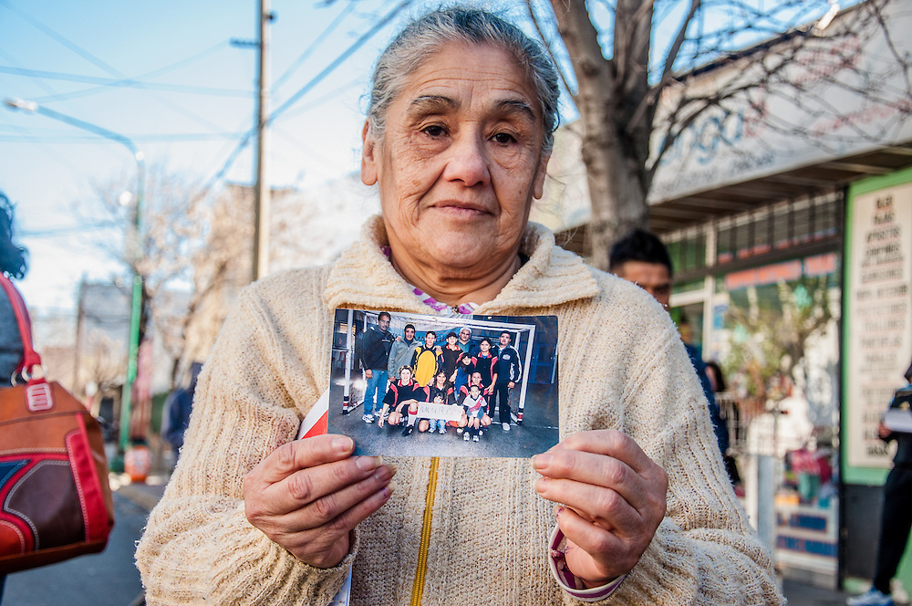 2015, Buenos Aires, Argentina. A woman shows a picture of her grandaughter and her friends during a demonstration to ask for justice after the girls' death.
